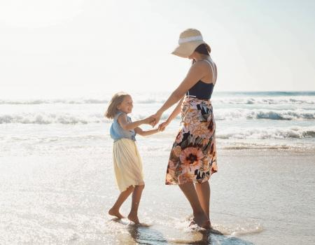 mother and daughter dancing on the beach