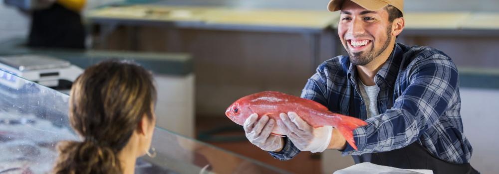 fishmonger handing a woman a fresh fish